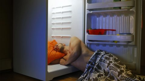 Man sleeping with his head in a refrigerator