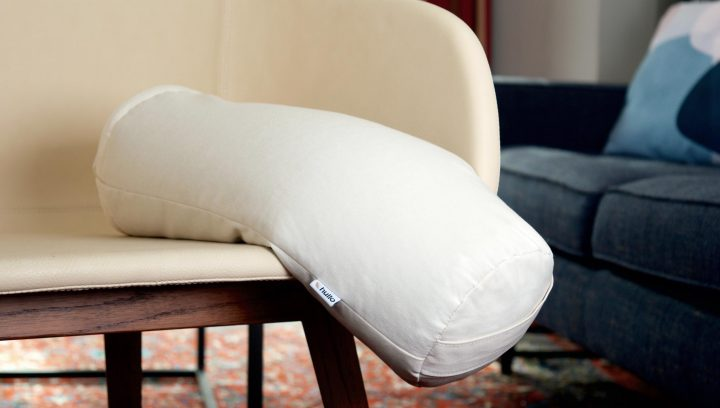 A buckwheat cervical pillow sits in a chair