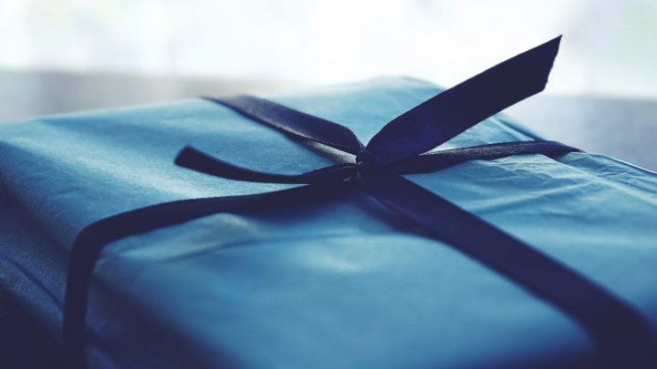 a present wrapped in blue paper with a bow