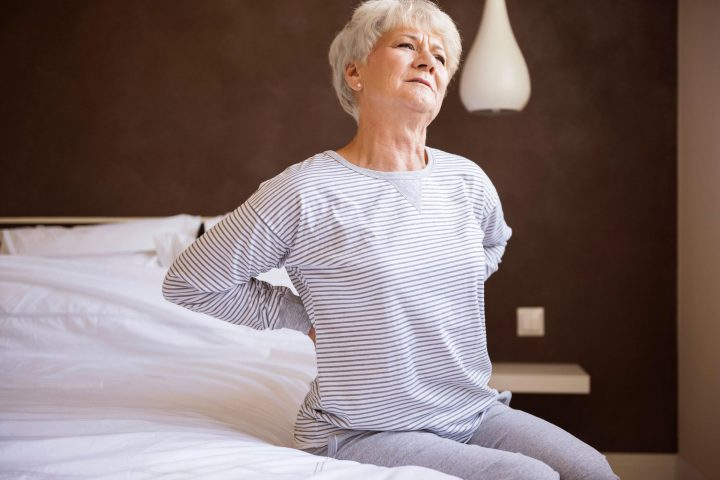 Woman sits on bed while stretching her aching back