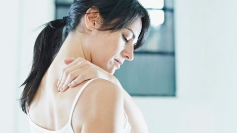 Woman rubs neck and shoulders
