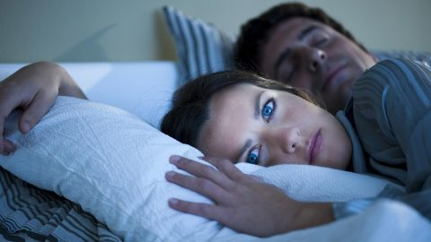Stressed woman lies awake in bed