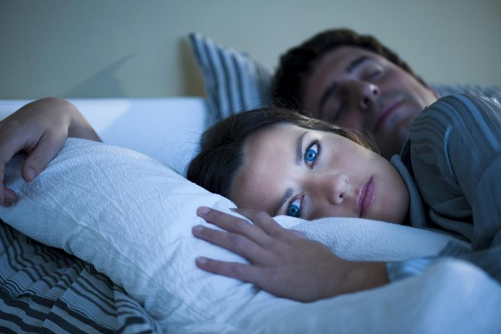 Woman lies awake in bed while her husband sleeps