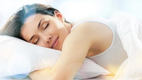 Woman sleeps with her arm under her pillow