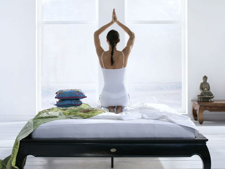 woman doing yoga on a bed